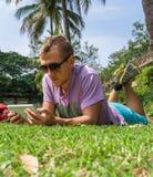 Equipe a colocação na grama e a utilização de sua tabuleta Fotos de Stock