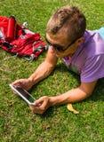 Equipe a colocação na grama e a utilização de sua tabuleta Fotos de Stock Royalty Free