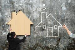 Equipe a colocação da casa de madeira no furo do muro de cimento Fotografia de Stock