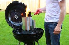 Equipe começar o fogo da chaminé de carvão do BBQ com isqueiro foto de stock