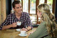 Equipe comer o café ao falar com a mulher no café fotografia de stock