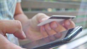 Equipe a compra em linha com o cartão vermelho do smartphone e de crédito vídeos de arquivo