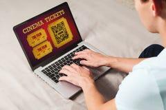 Equipe a compra na linha bilhetes do cinema no Internet com um portátil ao sentar-se em casa imagens de stock