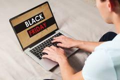 Equipe a compra no special de Black Friday pelo Internet com um portátil ao sentar-se em casa fotografia de stock