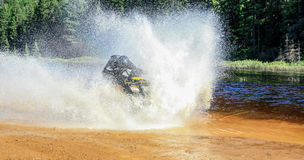Equipe a condução do quadrilátero de ATV com do espirro da água com a alta velocidade Foto de Stock