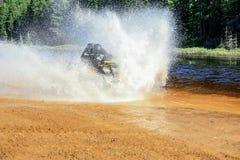 Equipe a condução do quadrilátero de ATV com do espirro da água com a alta velocidade Fotografia de Stock