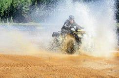 Equipe a condução do quadrilátero de ATV com do espirro da água com a alta velocidade Foto de Stock Royalty Free