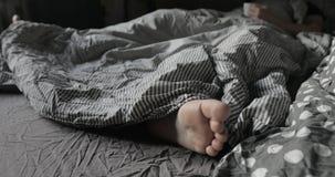 Equipe a configuração sob a cobertura da cama e os pés shoeless dos movimentos filme