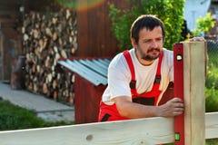 Equipe a construção de uma cerca de madeira - verificando com um nível Foto de Stock Royalty Free