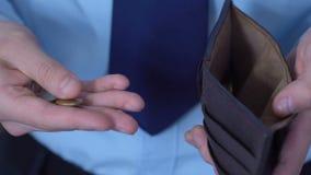 Equipe a contagem de poucas moedas, pondo as na bolsa, conceito da pobreza, baixo salário filme