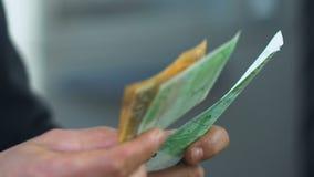 Equipe a contagem do close-up dos euro, recebendo o dinheiro social da permissão no banco, negócio vídeos de arquivo