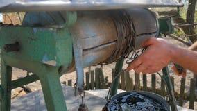 Equipe a corrente das gotas com a cubeta em rústico bem para tirar a água vídeos de arquivo