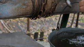 Equipe a corrente das gotas com a cubeta em rústico bem para tirar a água Água suja filme