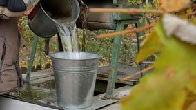 Equipe a corrente das gotas com a cubeta em rústico bem para tirar a água Água suja video estoque
