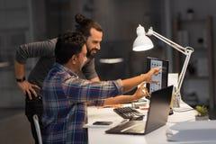 Equipe criativa com o computador que trabalha tarde no escritório foto de stock