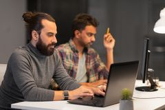 Equipe criativa com o computador que trabalha tarde no escrit?rio imagens de stock