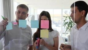 A equipe criativa do negócio cola das etiquetas à parede de vidro no espaço de escritórios vídeos de arquivo