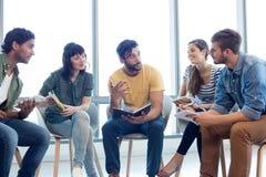 Equipe criativa do negócio que discute com seus diários Imagens de Stock
