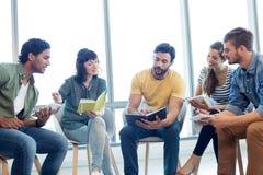 Equipe criativa do negócio que discute com seus diários Imagem de Stock