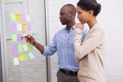 Equipe criativa do negócio que olha notas pegajosas na janela Fotos de Stock Royalty Free