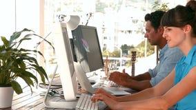 Equipe criativa do negócio que trabalha junto no computador filme