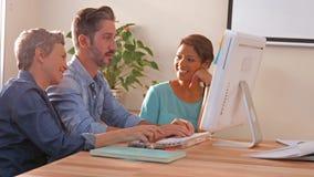 Equipe criativa do negócio que usa o computador e olhando a câmera filme