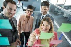 Equipe criativa do negócio que olha notas pegajosas Fotos de Stock