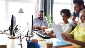 Equipe criativa feliz com os computadores no escritório