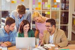 Equipe criativa feliz do negócio que usa o portátil na reunião imagens de stock