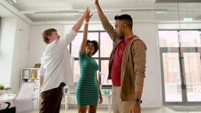 Equipe criativa feliz que faz a elevação cinco no escritório vídeos de arquivo