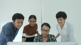 Equipe criativa ocasional do negócio que olha um tela de computador video estoque
