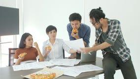 Equipe criativa ocasional do negócio que tem o almoço ao encontrar-se no escritório vídeos de arquivo
