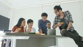 Equipe criativa ocasional do negócio que tem o almoço ao encontrar-se no escritório video estoque