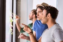 Equipe criativa que discute a informação em papéis pequenos Fotos de Stock Royalty Free
