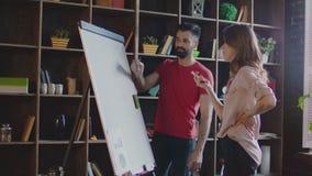 Equipe criativa que discute o plano de negócios na placa do marcador no escritório teamwork vídeos de arquivo