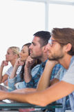 Equipe criativa que senta-se em uma linha que escuta algo Fotografia de Stock Royalty Free
