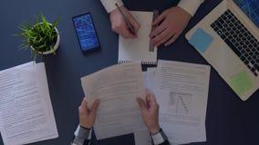 Equipe criativa que trabalha em um projeto do negócio no escritório que senta-se na tabela durante o dia tempo acelerado video estoque
