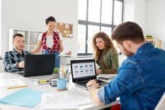 Equipe criativa que trabalha na interface de utilizador no escritório imagem de stock