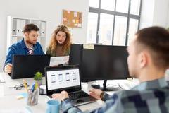 Equipe criativa que trabalha na interface de utilizador no escritório foto de stock