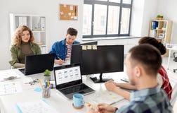 Equipe criativa que trabalha na interface de utilizador no escritório imagem de stock royalty free