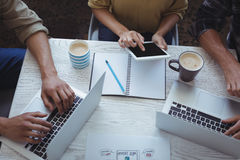 Equipe criativa que usa o portátil e a tabuleta digital ao planear no escritório foto de stock