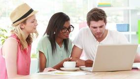 Equipe criativa que usa um portátil junto vídeos de arquivo