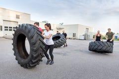 Equipe da aptidão que lança pneus pesados como o exercício Fotografia de Stock Royalty Free