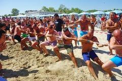 Equipe da competição de Tug War Men Beach Intense Foto de Stock
