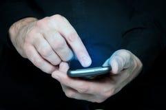 Equipe a dactilografia de uma mensagem de texto em um smartphone Imagens de Stock