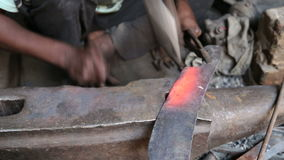 Equipe dar forma à lâmina caloroso com o malho na pedra na oficina em Varanasi vídeos de arquivo