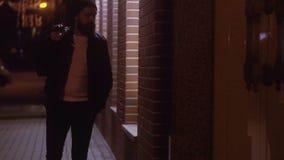 Equipe dar uma volta através da cidade da noite que passa através das janelas da loja vídeos de arquivo