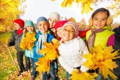 A equipe das crianças com ancinho e amarelo deixa grupos fotos de stock