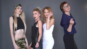 A equipe das meninas está dançando na roupa à moda, sorrindo na câmera isolada sobre o fundo preto Mulheres novas bonitas video estoque
