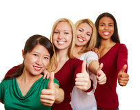 Equipe das mulheres multiculturais que mantêm os polegares fotos de stock